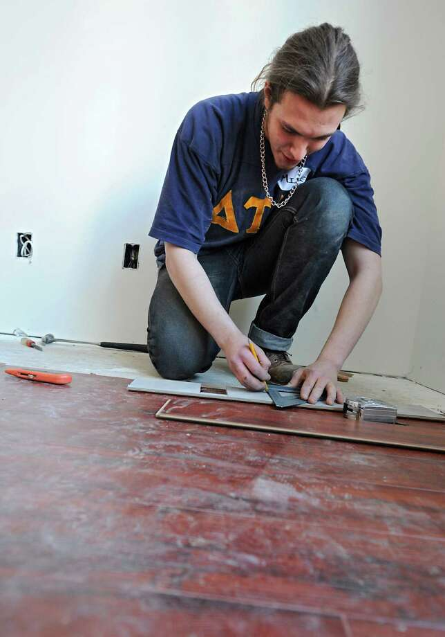 Habitat for Humanity volunteer Sam Guagliardo, a RPI student, works on a flooring project at Sheridan Hollow on Tuesday, Feb. 17, 2015 in Albany, N.Y. In upcoming weeks crews at the houses could increase as the nonprofit starts a program with the Albany County Sheriff that would use inmates to work on the homes. (Lori Van Buren / Times Union) Photo: Lori Van Buren / 00030656A