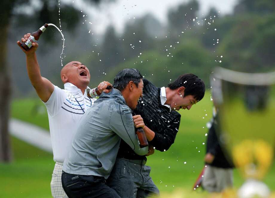 A soggy day at Riviera Country Club in Los Angeles becomes even sloppier as fellow players Jason Oh, left, and Noh Seung-Yul, right, use beer to celebrate James Hahn's first PGA Tour victory. Photo: Mark J. Terrill, STF / AP