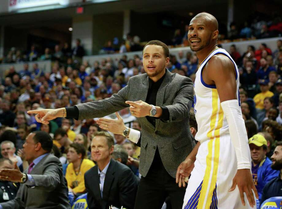 Due to a sore ankle, the Warriors' Stephen Curry could only contribute in limited ways like joining  Leandro Barbosa, right, in questioning a call. Photo: R Brent Smith, FRE / AP
