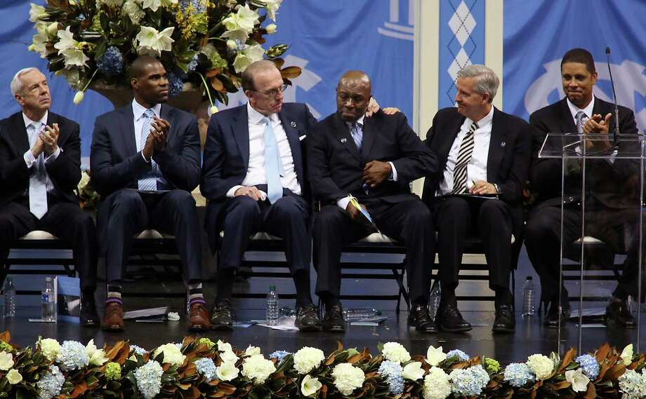 Billy Cunningham, third from left, and David Chadwick, second from right, comfort fellow former North Carolina basketball Phil Ford during a memorial service for former North Carolina basketball coach Dean Smith, Sunday, Feb. 22, 2015, at the Smith Center in Chapel Hill, N.C. Smith died at 83 earlier in February. Also pictured are current UNC basketball coach Roy Williams, from left, and former UNC player Antawn Jamison. (AP Photo/Ted Richardson) Photo: Ted Richardson, FRE / AP