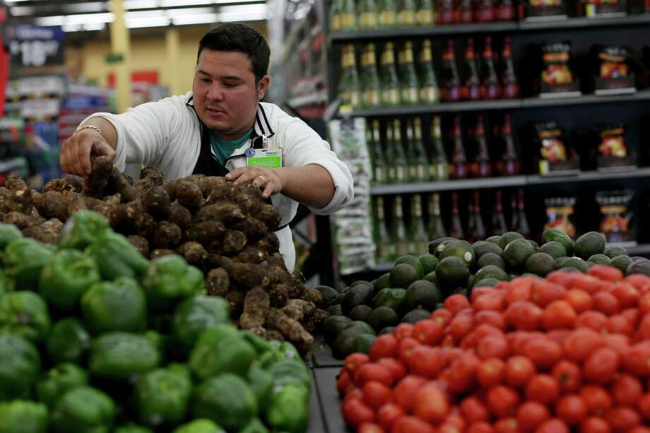 MIAMI, FL - FEBRUARY 19:  Walmart employee Dayngel Fernandez works in the produce department stocking shelves at a Walmart store on February 19, 2015 in Miami, Florida.  The Walmart company announced Thursday that it will raise the wages of its store employees to $10 per hour by next February, bringing pay hikes to an estimated 500,000 workers. Photo: Joe Raedle, Getty Images / 2015 Getty Images