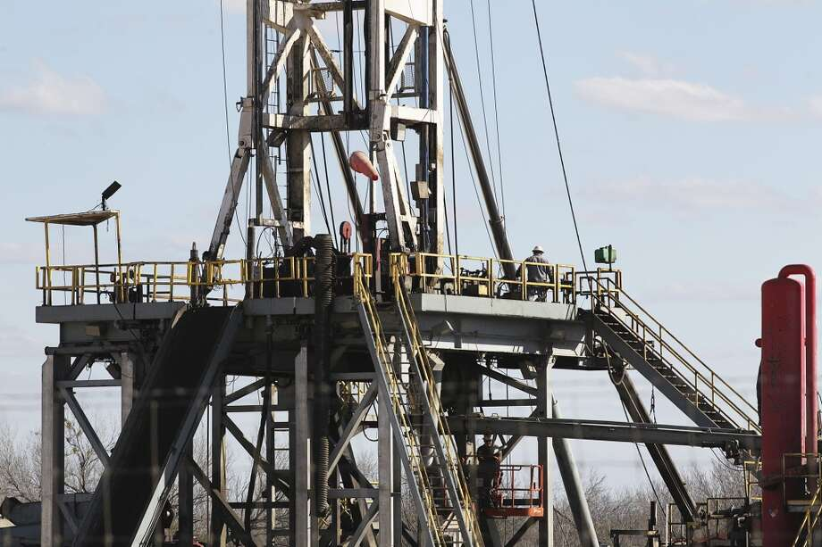 Work continues on a drilling rig off Texas State Highway 72 east of Tilden, Texas, Thursday, February, 19, 2015. A drop in the price of crude oil from has led to lower prices at the pump for consumers. Hovering close to $50 from a high of over $100 per barrel of oil has led to a slow down activity in the Eagle Ford Shale play. Photo: JERRY LARA, San Antonio Express-News