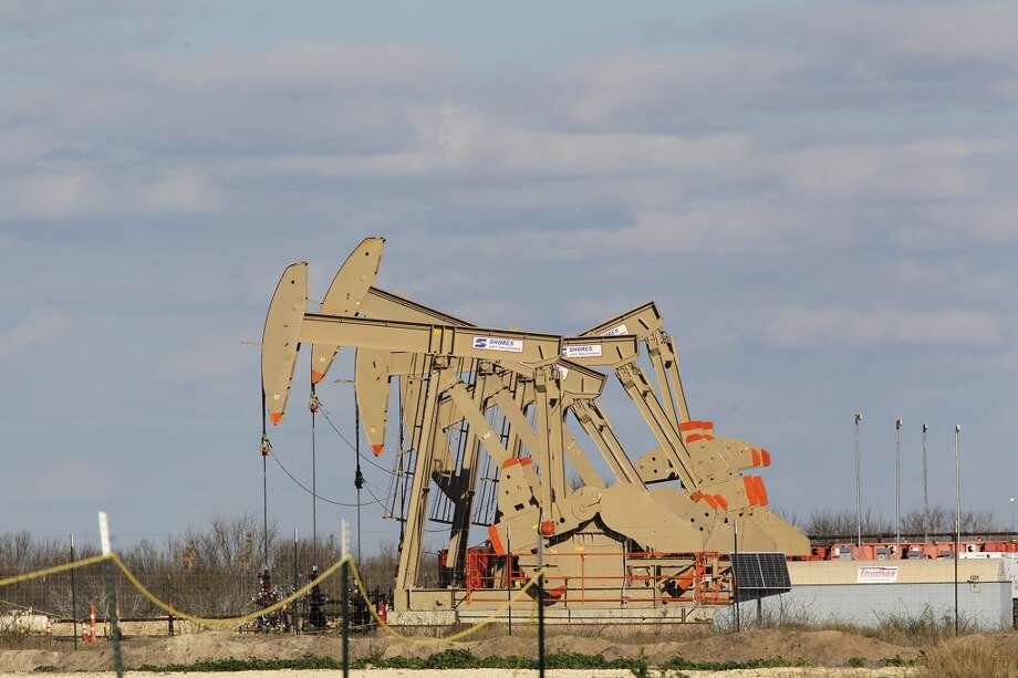Pump jacks extract oil and gas from the Eagle Ford Shale at a pad off Texas State Highway 72. Photo: JERRY LARA, San Antonio Express-News