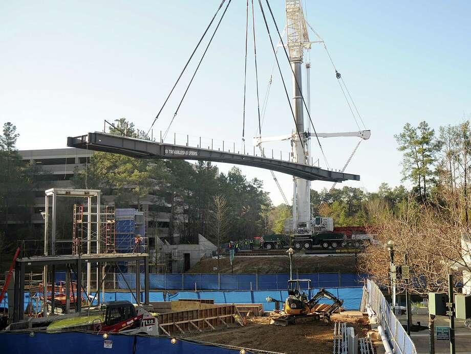 A crane lifts a segment of the new  pedestrian bridge over The Woodlands Waterway. The bridge will be located near the new Westin Hotel. Photo: David Hopper, Freelance / freelance