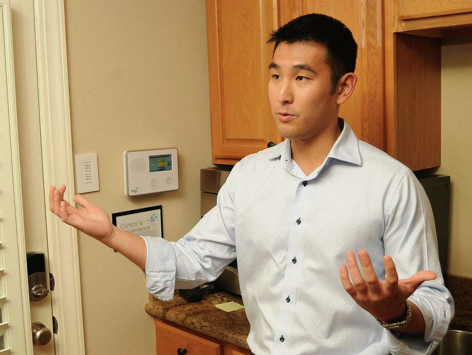 Dean Chuang, a product manager for NRG Energy, explains the security panel at the NRG Smart House in Montrose, which serves as a showroom for the company's products and services. Photo: Dave Rossman, Freelance / Freelalnce