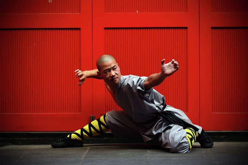 A Shaolin Monk Poses For A Photograph In Chinatown On