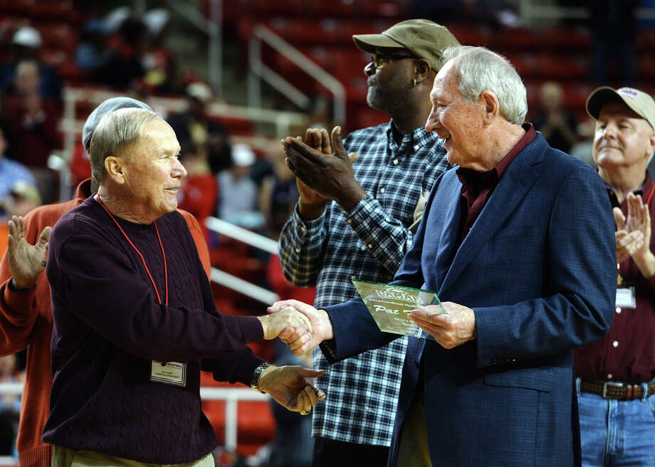 Former Lamar basketball coaches Billy Tubbs, left, and Pat Foster shake hands during Saturday's reunion. The Lamar Cardinals held a men's basketball reunion during the halftime of Saturday night's game against McNeese State.  Photo taken Saturday 2/21/15  Jake Daniels/The Enterprise Photo: Jake Daniels / ©2014 The Beaumont Enterprise/Jake Daniels