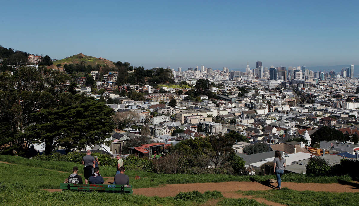 Visitors admire the view and enjoy the weather from Kite Hill Open Space on a sunny San Francisco day.