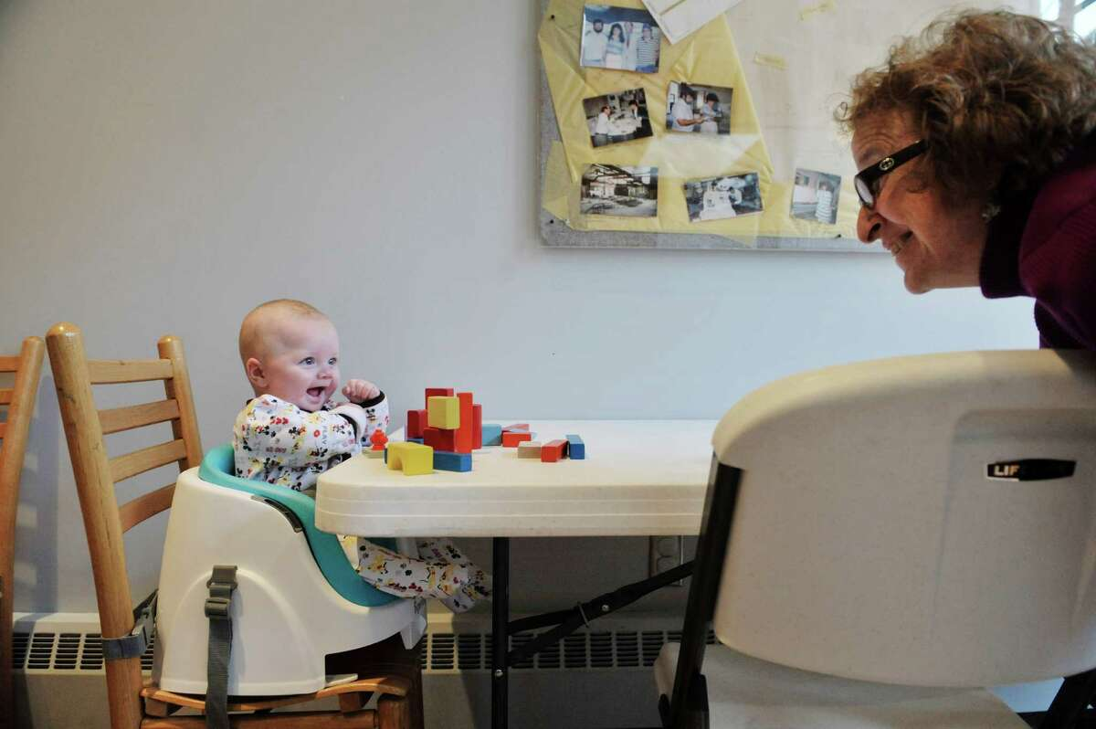 Garrus Tubbs, four months old, from Schenectady works with blocks with Carol Ann Margolis, education coordinator, at The Building Blocks of the City Room program at the Albany Heritage Area Visitors Center on Monday, Feb. 23, 2015, in Albany, N.Y. The program is held on the last Monday morning of each month and is free for children accompanied by adults to learn about architecture and building construction. Children and adults can use various types of building blocks to create structures. Margolis said the program, which was going to end after this month, will continue to run every month going forward. (Paul Buckowski / Times Union)