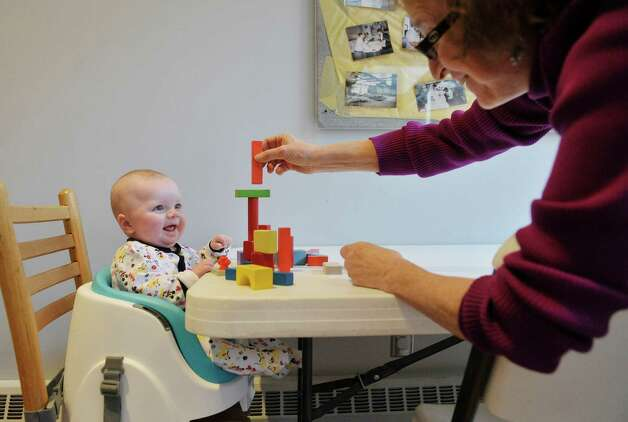 Garrus Tubbs, four months old, from Schenectady works with blocks with Carol Ann Margolis, education coordinator, at The Building Blocks of the City Room program at the Albany Heritage Area Visitors Center on Monday, Feb. 23, 2015, in Albany, N.Y. The program is held on the last Monday morning of each month and is free for children accompanied by adults to learn about architecture and building construction.  Children and adults can use various types of building blocks to create structures.  Margolis said the program, which was going to end after this month, will continue to run every month going forward.  (Paul Buckowski / Times Union) Photo: PAUL BUCKOWSKI / 00030095A