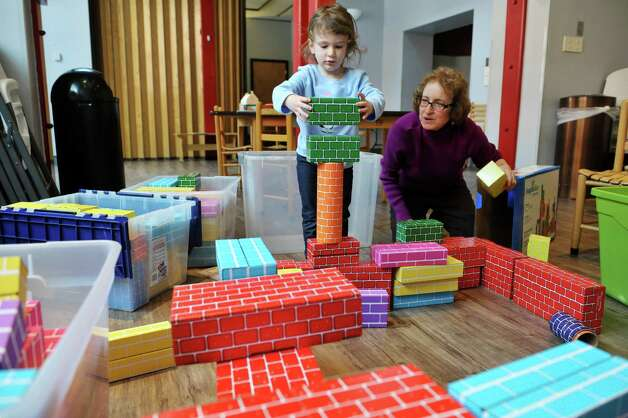 Nava Shear, 3, from Delmar stacks some blocks as she and Carol Ann Margolis, education coordinator, create a structure at The Building Blocks of the City Room program at the Albany Heritage Area Visitors Center on Monday, Feb. 23, 2015, in Albany, N.Y. (Paul Buckowski / Times Union) Photo: PAUL BUCKOWSKI / 00030095A