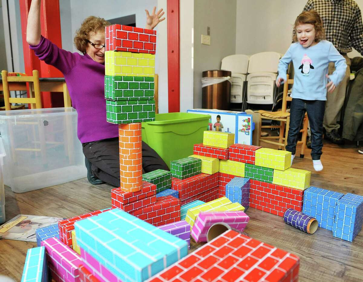 Carol Ann Margolis, left, education coordinator, and Nava Shear, 3, from Delmar celebrate as some blocks they placed stay up at The Building Blocks of the City Room program at the Albany Heritage Area Visitors Center on Monday, Feb. 23, 2015, in Albany, N.Y. (Paul Buckowski / Times Union)
