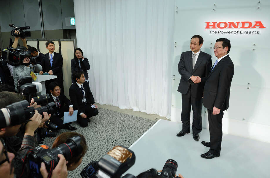 Takanobu Ito (left), the outgoing president of Honda Motor Co., shakes hands with his replacement, Takahiro Hachigo, at a news conference in Tokyo. Photo: Akio Kon / Bloomberg / © 2015 Bloomberg Finance LP