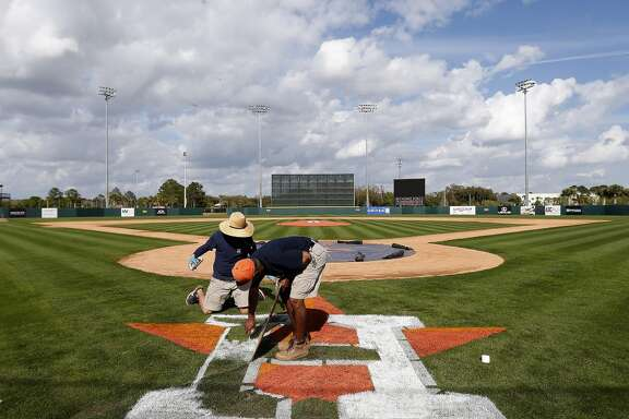 Osceola County groundskeepers Tomas Lebron and Wayne Thompson work on painting the Houston Astros logo on the field at the Osceola County Stadium, Monday, Feb. 23, 2015, in Kissimmee. ( Karen Warren / Houston Chronicle  )