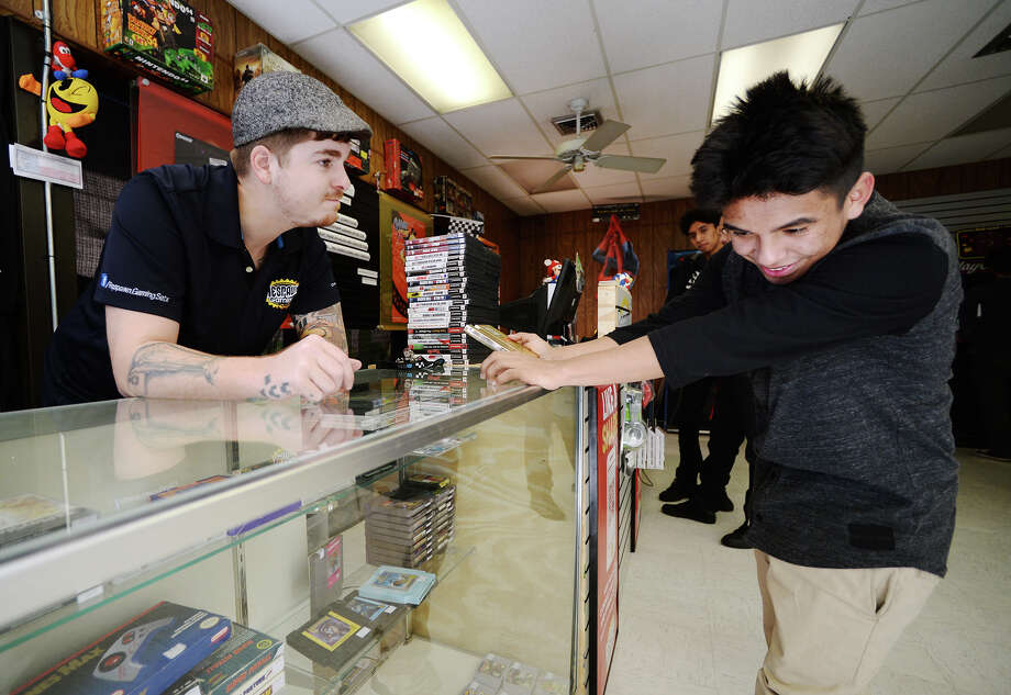Austin Sonnier, left, talks about some of the Nintendo games in stock at Respawn Gaming with Abraham Castro on Thursday afternoon. Respawn Gaming, a shop specializing in used and preowned video game equipment and games, opened about three weeks ago.  Photo taken Thursday 2/19/15  Jake Daniels/The Enterprise Photo: Jake Daniels / ©2014 The Beaumont Enterprise/Jake Daniels