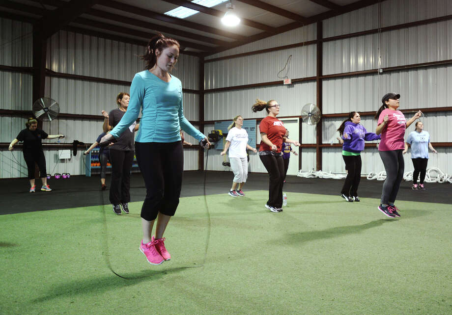 Jessica Wyble, front left, and others warm up for a workout at Delta Life Bootcamp on Monday afternoon. Delta Life Bootcamp has been helping people shed pounds at their mid-county location since last September. Aside from exercise and weight tracking, coaches help motivate attendees regarding healthier lifestyles.  Photo taken Monday 1/26/15 Jake Daniels/The Enterprise Photo: Jake Daniels / ©2014 The Beaumont Enterprise/Jake Daniels