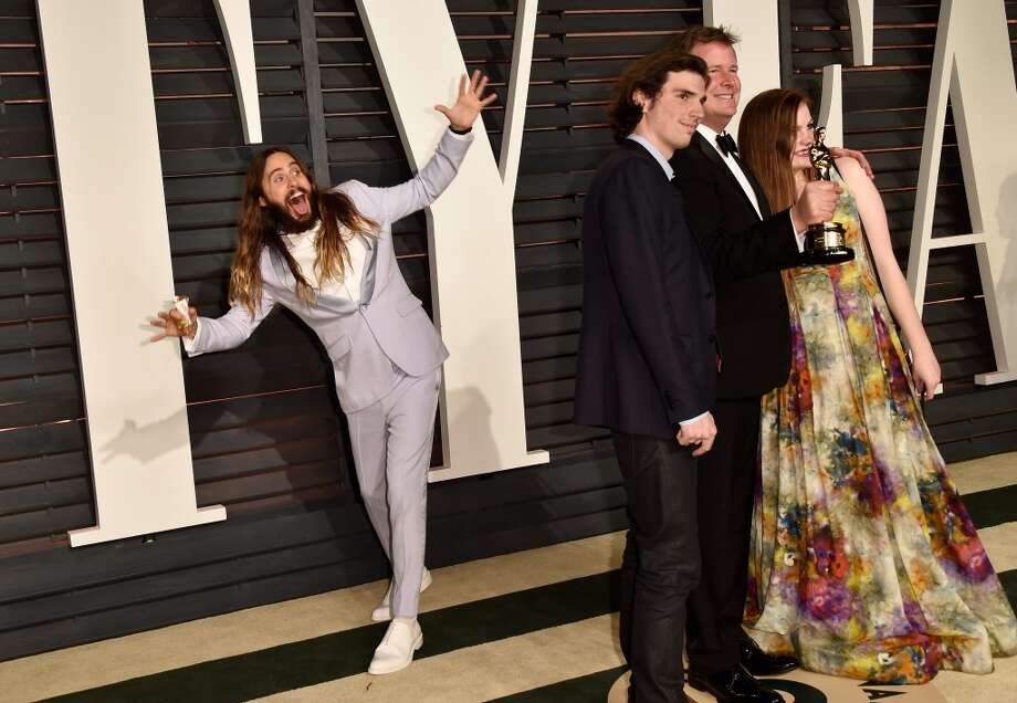 Actor Jared Leto photobombs producer James W. Skotchdopole (2nd from right) and guests at the 2015 Vanity Fair Oscar Party hosted by Graydon Carter at Wallis Annenberg Center for the Performing Arts on February 22, 2015 in Beverly Hills, California. (Photo by Pascal Le Segretain/Getty Images)