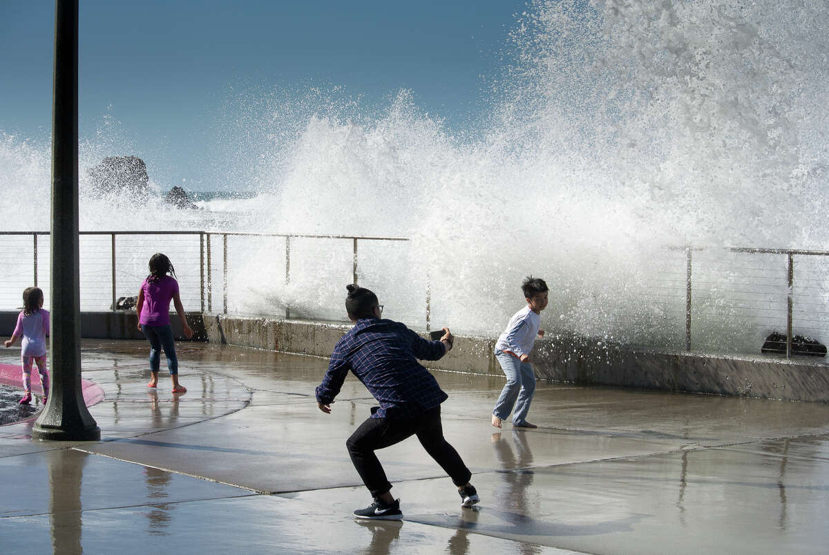 A photo from 2015 shows people playing keep-away with the crashing breakers on Rockaway's seawall.