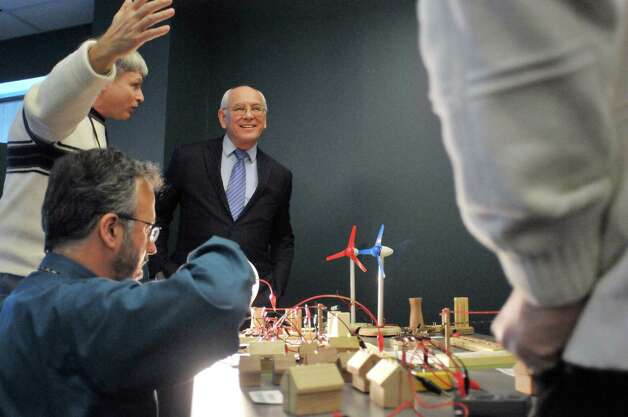STEM Class teacher John Hartnett, foreground left, and Glenn Van Knowe, background left, vice president and senior scientist at Meso, Inc. inTroy, show Congressman Paul Tonko a model, designed by Van Knowe, that has a network of different sources of energy, different demands on the energy and different ways to connect to the energy at Tech Valley High School on Monday, Feb. 23, 2015, in Albany, N.Y.  Van Knowe is working with teachers and students at the school in a two-year program funded through a NYSERDA grant to promote engineering in the STEM education program.   (Paul Buckowski / Times Union) Photo: PAUL BUCKOWSKI / 00030720A