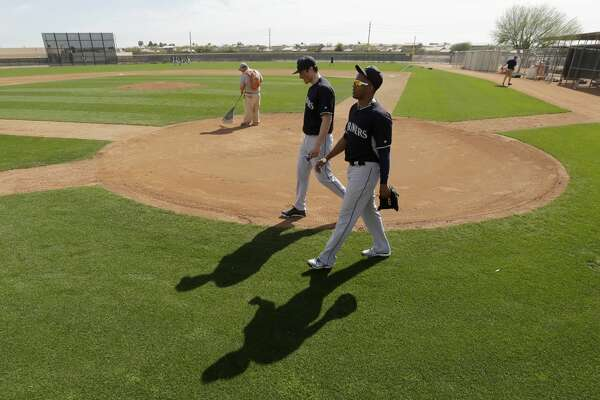 Seattle Mariners' Roenis Elias, right, and Michael Kickham walk to the clubhouse after spring training baseball practice Saturday, Feb. 21, 2015, in Peoria, Ariz. (AP Photo/Charlie Riedel)
