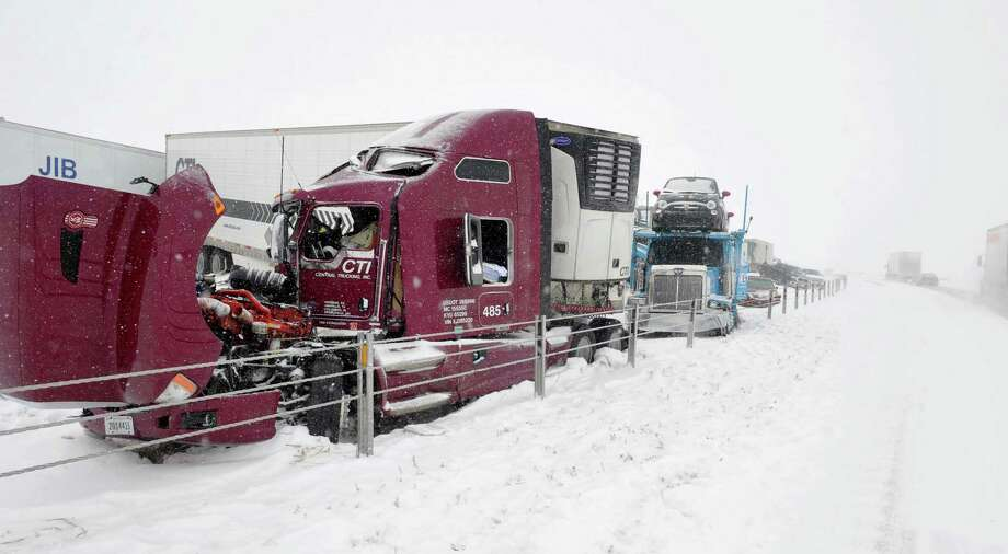 Officials work to document the accident and clear wreckage at the scene after a major pileup involving more than 2 dozen vehicles closed Interstate 40 eastbound traffic near Hope Road, 10 miles west of Amarillo, Texas, Monday, Feb. 23, 2015. Freezing rain affected travel in nearly half of Texas on Monday, and winter storm warnings were issued in the northern part of the state. (AP Photo/Amarillo Globe-News, Michael Schumacher) Photo: Michael Schumacher, Dylan Baddour / Amarillo Globe-News