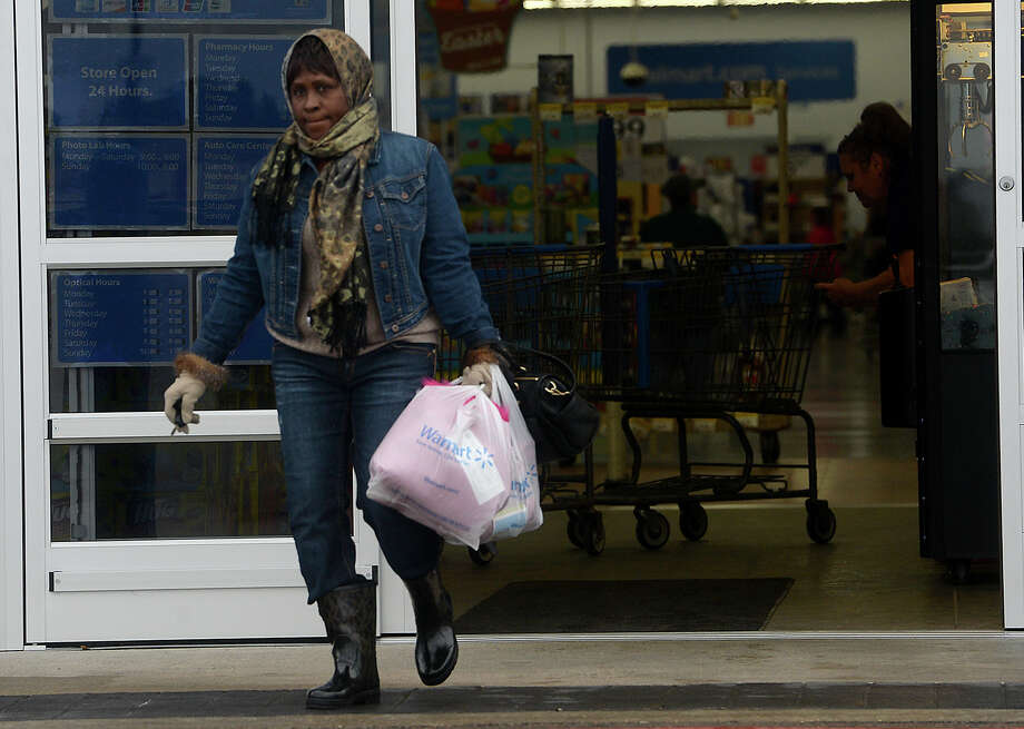 Shopper Sarah Sells is bundled up against the cold as she makes her way out of the Walmart store in Lumberton Monday. A cold snap has descended on the area, bringing with it wind and rain. Photo taken Monday, February 23, 2015 Kim Brent/The Enterprise Photo: Kim Brent / Beaumont Enterprise