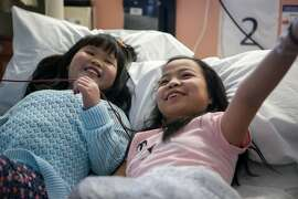 Left to right--Newly reunited best friends, Mai Frandsen,11,  and Mae Rainey, 11, pass the time in the hospital while Frandsen receives a blood transfusion in Oakland, Calif., on Monday, February 23, 2015.