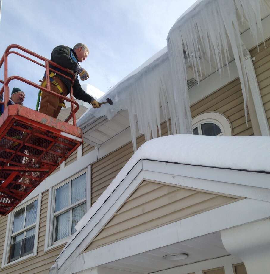 Icicles are in peak season this winter in the Capital Region. Dan Maguire submitted this image of Siena College employees clearing roofs to prevent ice dams on the Loudonville campus. (provided photo)