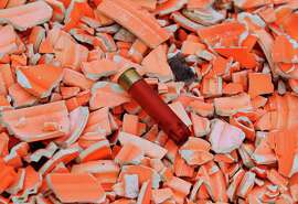 A spent shotgun shell lies in the rubble of clay pigeons on the skeet range at the Pacific Rod and Gun Club at Lake Merced.
