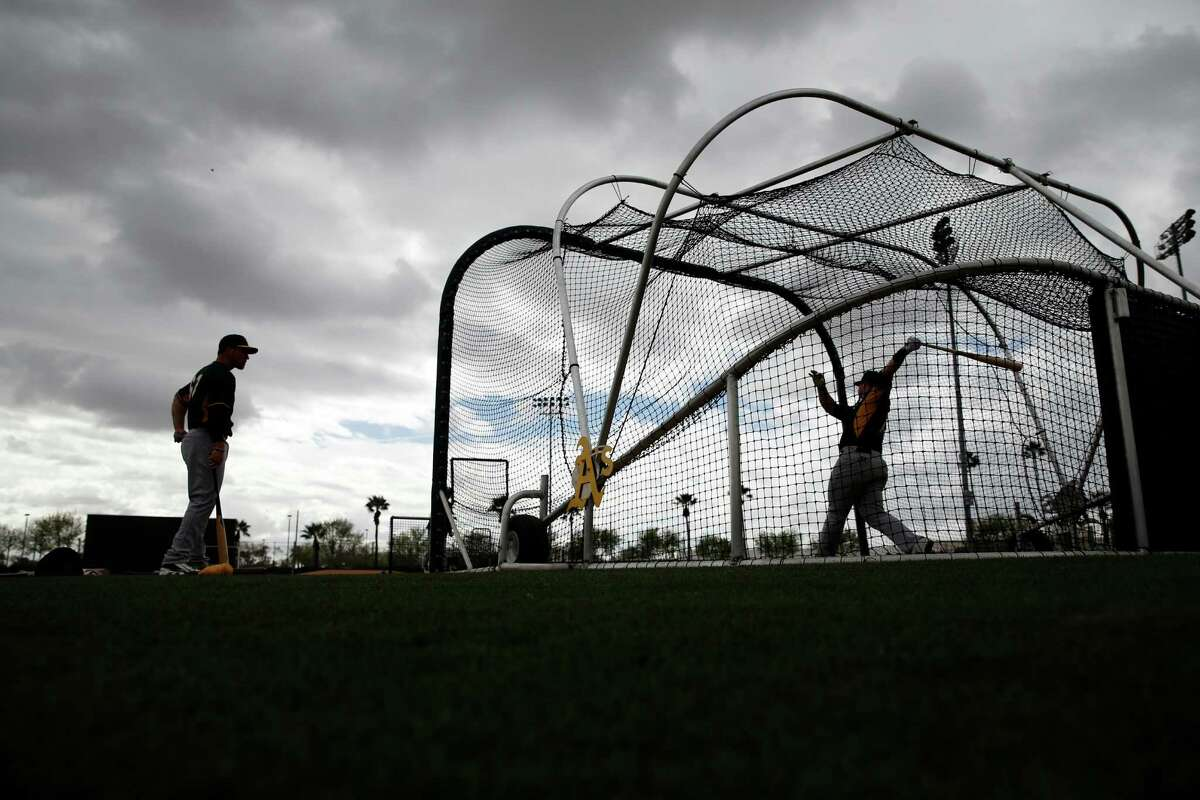 Oakland A's Josh Phegley takes a cut in the batting cage as Carson Blair waits his turn during Spring Training in Mesa, Arizona, on Monday, February 23, 2015.