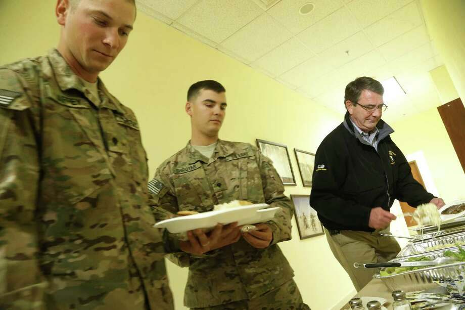 Secretary of Defense Ash Carter, right, goes through a lunch line with soldiers Sunday at Kandahar Airfield in Kandahar, Afghanistan. Carter, who was sworn in last week, is making his first trip to visit troops. Photo: Pool / 2015 Getty Images