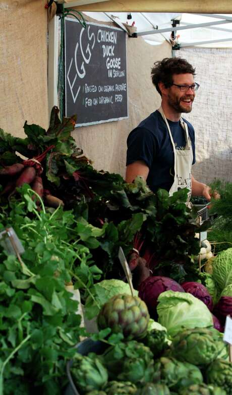 Josh Amaris of Eatwell Farm in Dixon helps customers at the Ferry Plaza Farmers Market. Photo: Sophia Germer / The Chronicle / ONLINE_YES