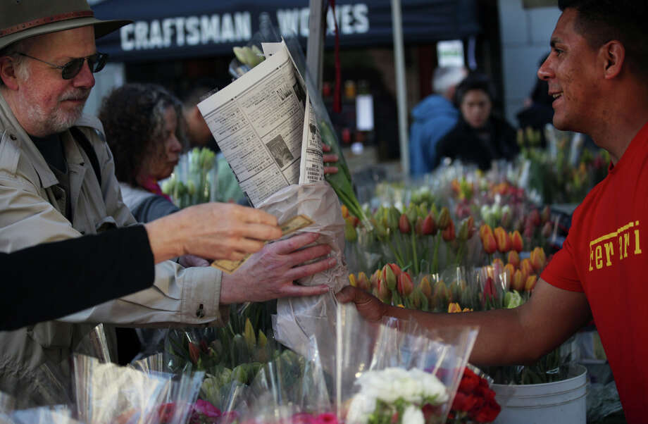 Reynaldo Magana sells flowers to a customer at the McGinnis Ranch stand at the Ferry Plaza Farmers Market. Photo: Sophia Germer / The Chronicle / ONLINE_YES
