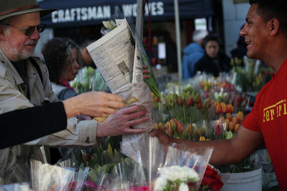Reynaldo Magana sells flowers to a customer at the McGinnis Ranch stand at the Ferry Plaza Farmers Market.
