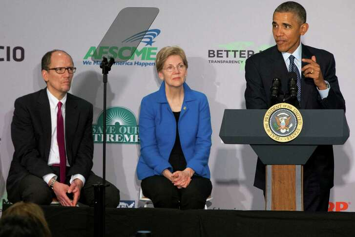 Labor Secretary Tom Perez, left, and Sen. Elizabeth Warren, D-Mass., listen as President Barack Obama speaks at AARP in Washington, Monday, Feb. 23, 2015. President Barack Obama says too few Americans approaching retirement have saved enough to have peace of mind during their later years. (AP Photo/Jacquelyn Martin)