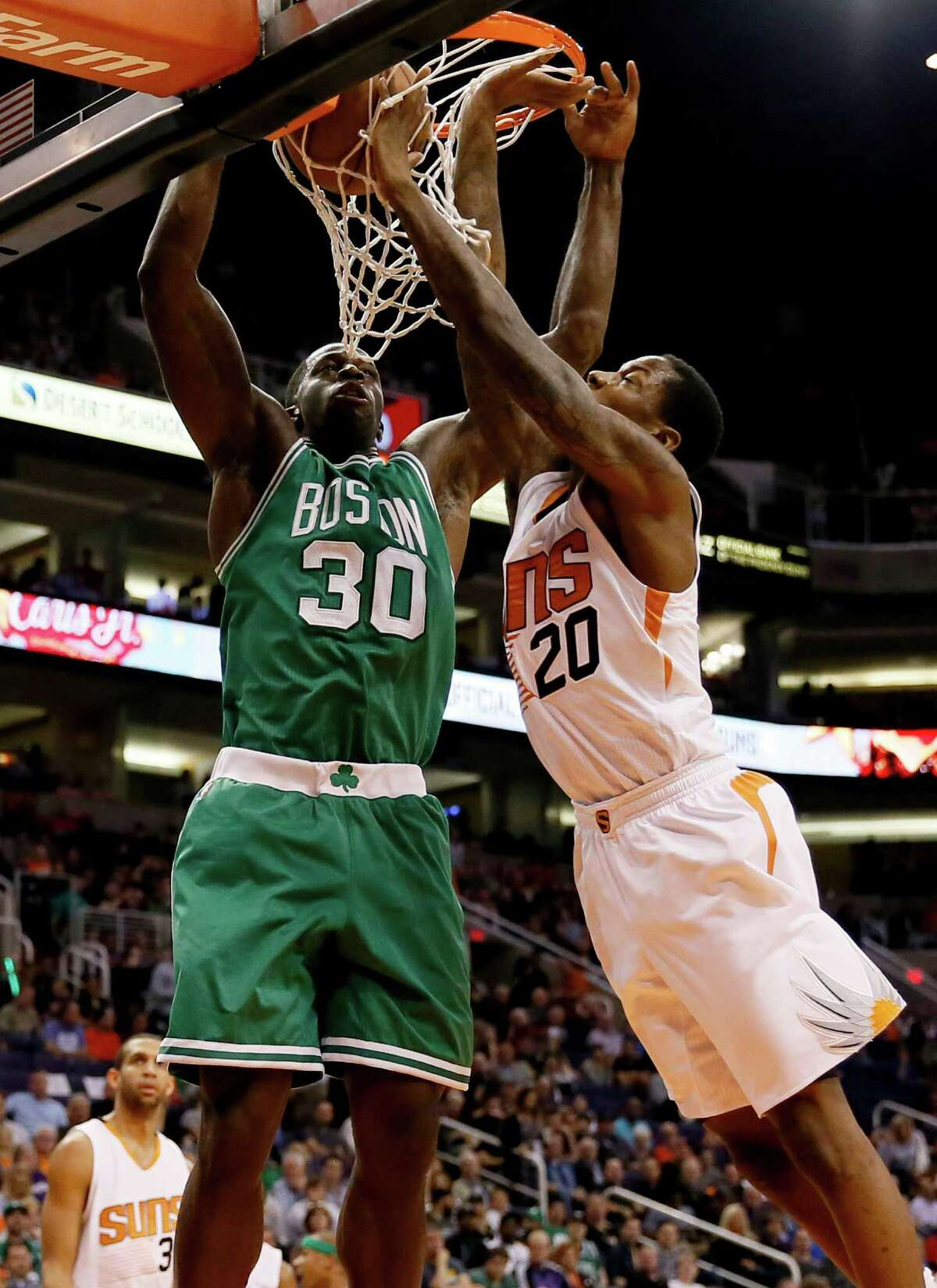 Boston Celtics' Brandon Bass (30) dunks over Phoenix Suns' Archie Goodwin during the first half of an NBA basketball game Monday, Feb. 23, 2015, in Phoenix. (AP Photo/Matt York) ORG XMIT: AZMY107