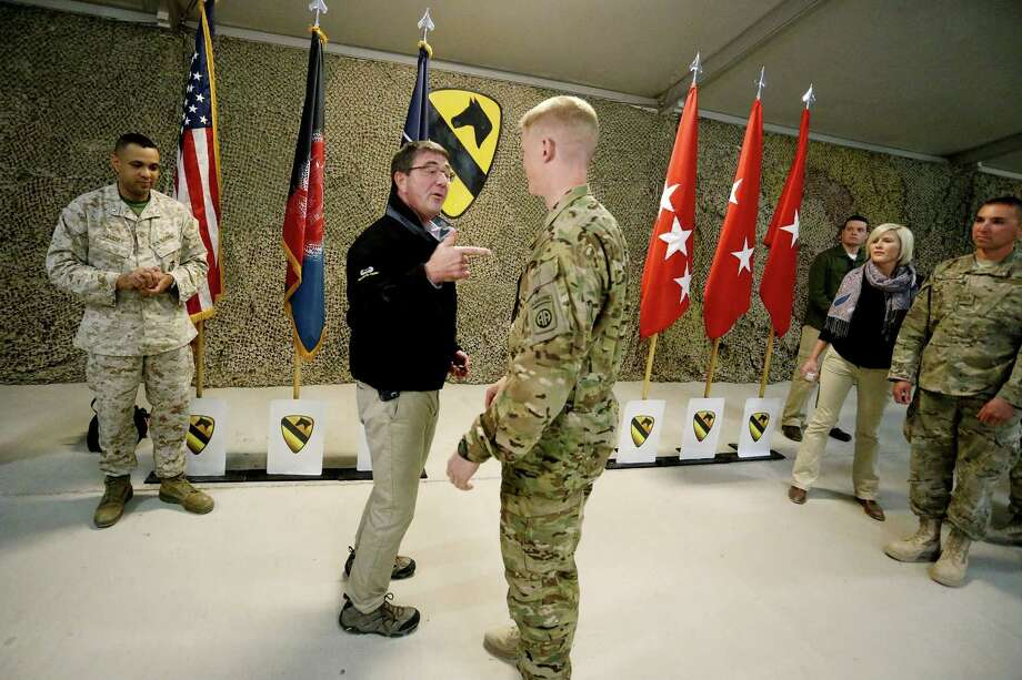 U.S. Defense Secretary Ash Carter, left, speaks with a soldier at Kandahar Airfield in Afghanistan, Sunday, Feb. 22, 2015. Carter is making his first trip to visit troops and commanders in Afghanistan since his swearing-in this week. (AP Photo/Jonathan Ernst, Pool) ORG XMIT: CAI126 Photo: Jonathan Ernst / Reuters Pool