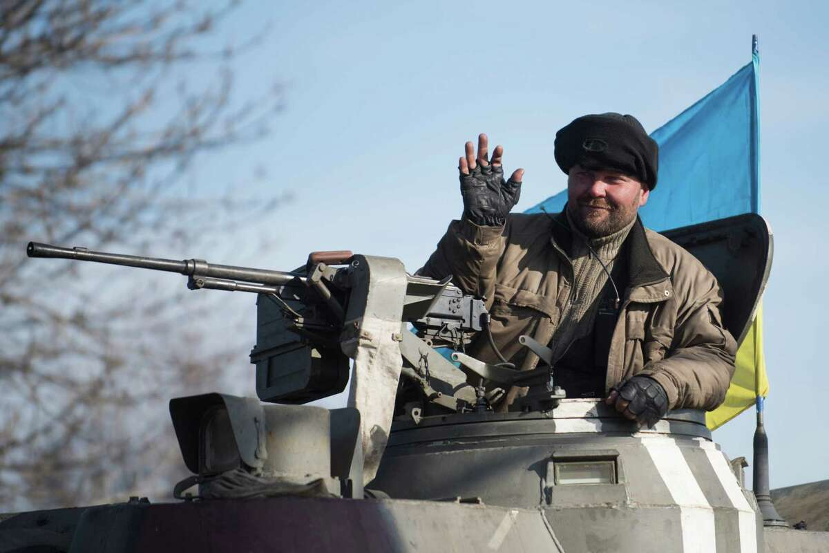 A Ukrainian soldier rides on an armored vehicle ahead of self-propelled artillery near Artemivsk, eastern Ukraine, Monday, Feb. 23, 2015. A Ukrainian military spokesman says continuing attacks from rebels are delaying Ukrainian forces' pullback of heavy weapons from the front line in the country's east. (AP Photo/Evgeniy Maloletka) ORG XMIT: XAZ116