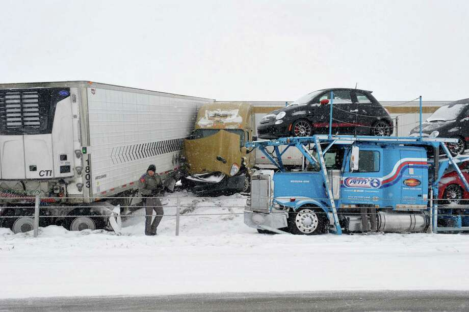 IN TEXAS: Officials work to document the accident and clear wreckage at the scene after a major pileup involving more than 2 dozen vehicles closed Interstate 40 eastbound traffic near Hope Road, 10 miles west of Amarillo, Texas, Monday, Feb. 23, 2015. Freezing rain affected travel in nearly half of Texas on Monday, and winter storm warnings were issued in the northern part of the state. (AP Photo/Amarillo Globe-News, Michael Schumacher) Photo: Michael Schumacher / Associated Press / Amarillo Globe-News