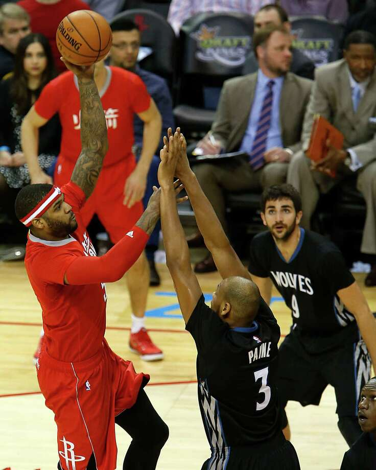 Rockets forward Josh Smith, left, shoots over the Timberwolves' Adreian Payne in a game that had the fashion twist of featuring uniforms with sleeves for both teams. Photo: James Nielsen, Staff / © 2015  Houston Chronicle