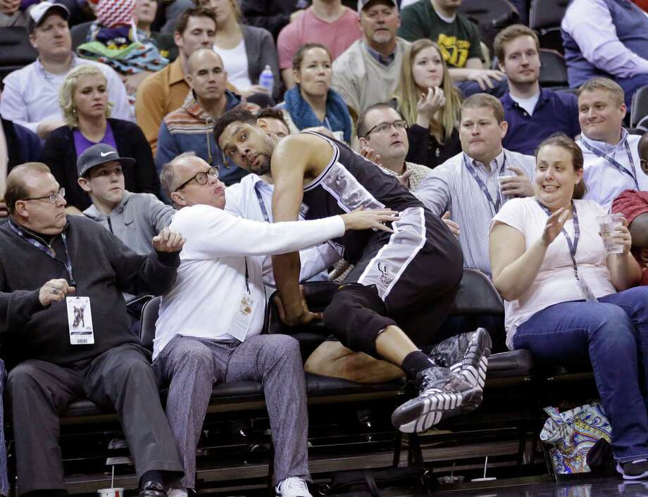 Tim Duncan falls in to the stands in the second half of the Spurs 90-81 loss to the Jazz in Salt Lake City Monday. Photo: Rick Bowmer /Associated Press / AP