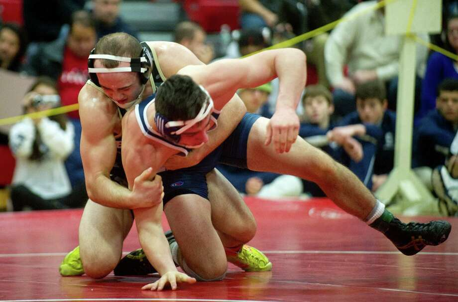 Charles Lomanto of Staples competes against Stephen Briganti of Trumbull, who won the match, during Saturday's FCIAC wrestling championship finals at New Canaan High School on February 14, 2015. Photo: Lindsay Perry / Stamford Advocate