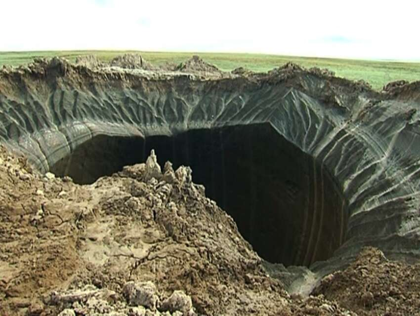 This frame grab made Wednesday, July 16, 2014, shows a crater, discovered recently in the Yamal Peninsula, in Yamalo-Nenets Autonomous Okrug, Russia. Russian scientists said Thursday July 17, 2014 that they believe a 60-meter wide crater, discovered recently in far northern Siberia, could be the result of changing temperatures in the region. Andrei Plekhanov, a senior researcher at the Scientific Research Center of the Arctic, traveled on Wednesday to the crater. Plekhanov said 80 percent of the crater appeared to be made up of ice and that there were no traces of an explosion, eliminating the possibility that a meteorite had struck the region. (AP Photo/Associated Press Television)