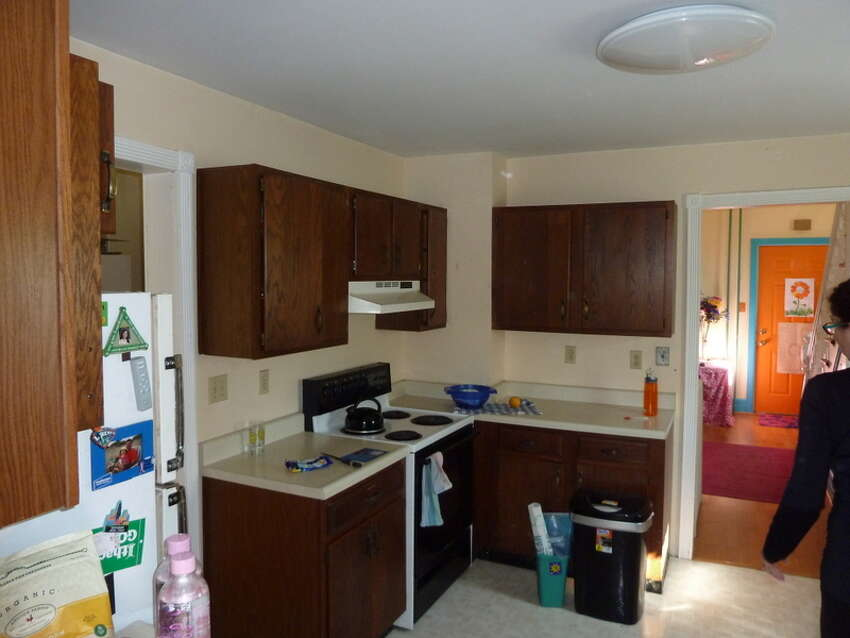 The entire kitchen was rearranged and these dark cabinets replaced. You can still see the orange door down the hall.