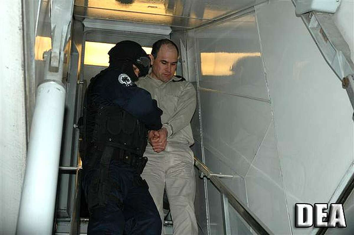 Osiel Cardenas Guillen, who was formerly the reputed principle leader of the Gulf Cartel is escorted by U.S. federal agents in January 2007, moments after stepping off a Mexican government plane that flew him to Houston to face criminal charges.