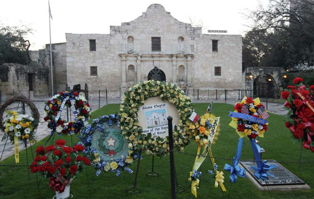"""Wreaths are placed near the front of the Alamo at the """"Dawn of the Alamo"""" remembrance and ceremony on March 7, 2014. A crowd gathered in the cold pre-dawn hours to mark the 178th anniversary of the battle for Texas independence. The solemn remembrance included a performance by a youth choir and musket volleys by members of the San Antonio Living History Association."""