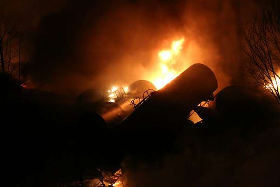 Derailed oil tanker train cars burn near Mount Carbon, W.Va., Monday, Feb. 16, 2015. A CSX train carrying more than 100 tankers of crude oil derailed in a snowstorm, sending a fireball into the sky and threatening the water supply of nearby residents, authorities and residents said Tuesday. (AP Photo/The Daily Mail, Marcus Constantino) Photo: Marcus Constantino, AP