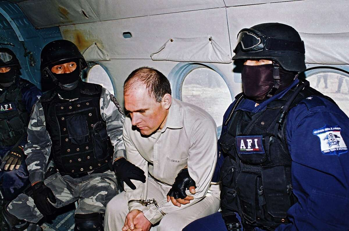 Head of the feared Gulf Cartel Osiel Cardenas Guillen (C) is guarded on a plane by members of the Federal Agency of Investigations (AFI) of Mexico, 20 January 2007, before being extradited to Houston. (HO/AFP/Getty Images)