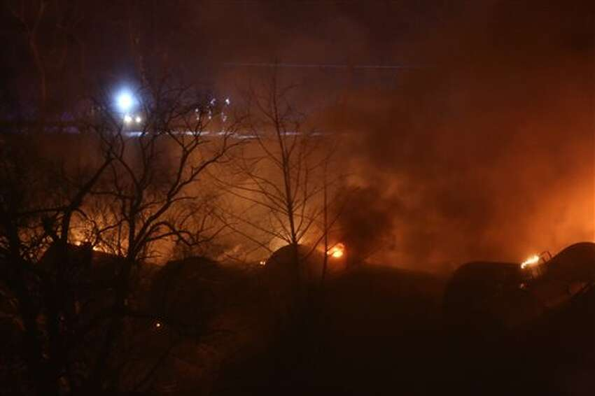 Firefighters look at burning train cars from W.Va. Route 61 near Mount Carbon, W.Va., Monday, Feb. 16, 2015. A CSX train carrying more than 100 tankers of crude oil derailed in a snowstorm, sending a fireball into the sky and threatening the water supply of nearby residents, authorities and residents said Tuesday. (AP Photo/The Daily Mail, Marcus Constantino)