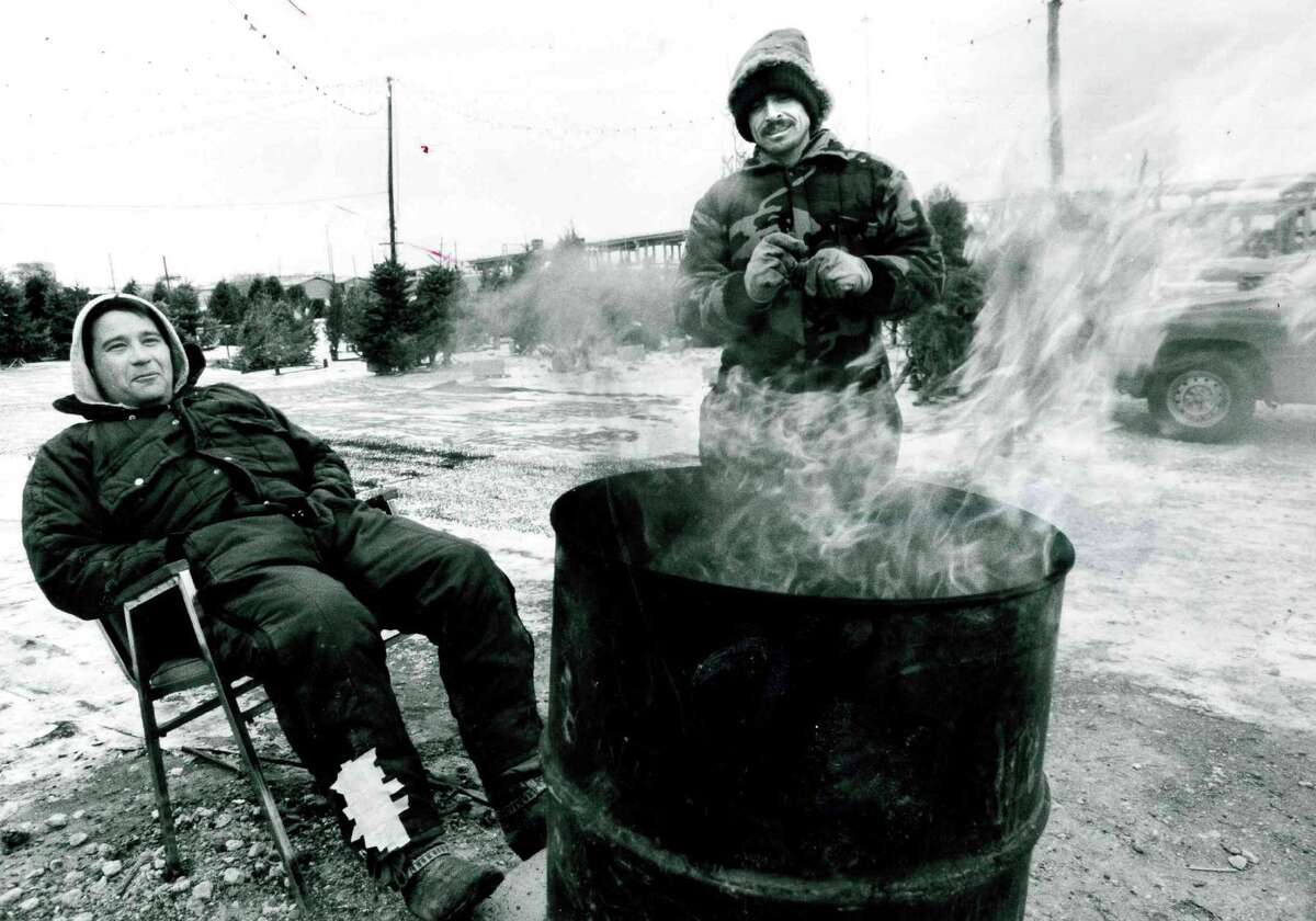 Check out these historic photos of Houstonians making the best of freezing temperatures. Glenn Bryant, left, and Luis Hernandez warm themselves around a barrel fire at a Christmas tree lot in the 5000 block of the Southwest Freeway on Dec. 23, 1989. Bryant, who operates the tree lot, said an ample supply of trees were left to buy but he was sold out of firewood.